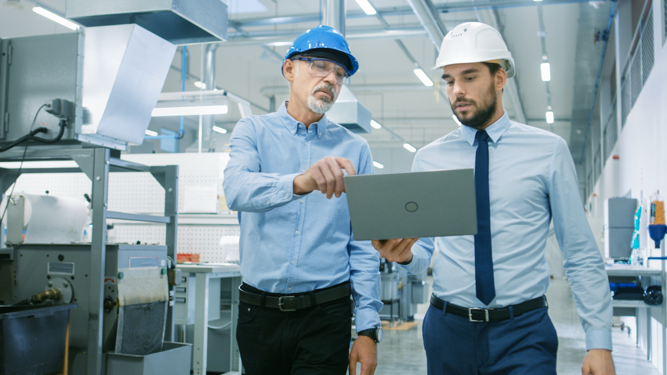 Head of the Department Holds Laptop and Discuss Product Details with Chief Engineer while They Walk Through Modern Factory.